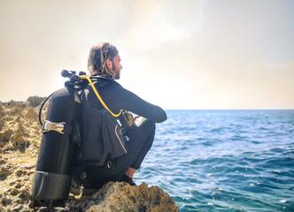 Płetwonurek siedzi na skale, patrząc na morze
