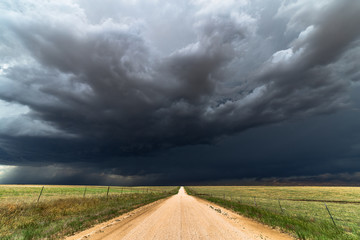 Dirt road with dark storm clouds