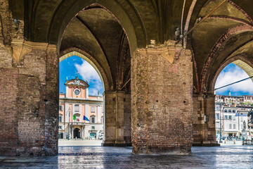 Piacenza, medieval town, Italy. Piazza Cavalli (Square horses) and Palazzo del Governatore  (Governor's palace) from the arcade of palazzo Gotico (Gothic palace) in the city center