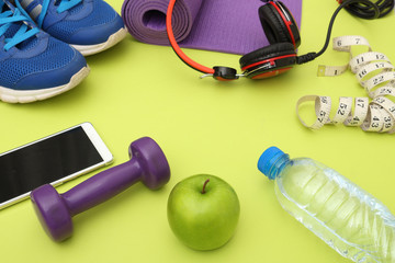 Athlete's set  dumbbells and bottle of water, Yoga mat, sport shoes,  on yellow  background. Concept healthy lifestyle, sport and diet. Sport equipment. Copy space