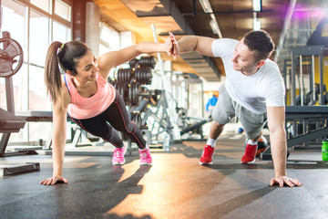 Young sporty couple working out together at gym.