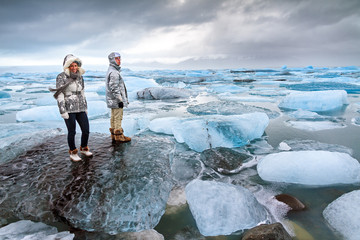 Extremely beautiful tourists stand on the massive icebergs in lake Jokulsarlon in Iceland in winter