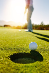Golf ball at the edge of hole with player in background