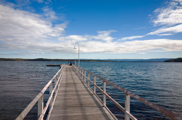 Anglers fishing from long Wooden Jetty on Lake Macquarie Australia