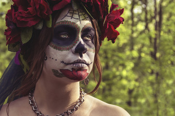 Beautiful woman  in makeup traditional Mexican Calavera skull Katrina in the autumn forest, in a wreath of red flowers. Day of the dead. Halloween celebration.
