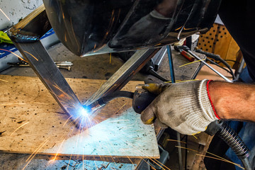man welds with a welding machine