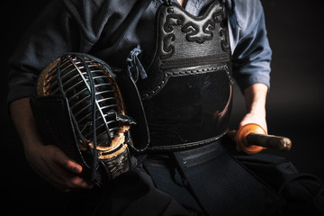 Kendo master standing in traditional armor .He holds japanese katana.