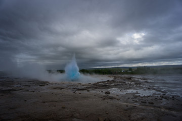 Iceland - Turquoise hot boiling water, beginning of eruption of geyser strokkur with trees