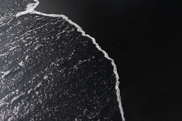 white ocean foam on black sand volcanic texture