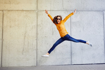 Joyful young lady jumping and raising arms in front of wall outside