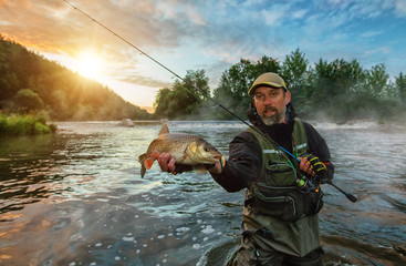 Sport fisherman holding trophy fish. Outdoor fishing in river