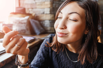 beautiful young asian woman sitting in a cafe and eating delicious cake