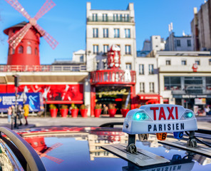 Parisian Taxi sign over blurred Paris boulevard.