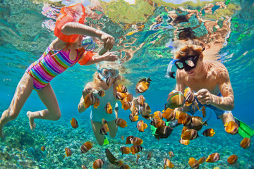 Szczęśliwa rodzina - ojciec, matka, dziecko w masce do nurkowania nurkować pod wodą z tropikalnymi rybami w basenie morskim rafy koralowej. Podróżuj stylem życia, przygodą ze sportem wodnym, pływaniem na wakacjach na plaży z dziećmi