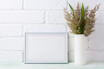 White landscape frame mockup with  grass and green leaves in cylinder vase