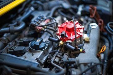 Reduktor gazu LPG przygotowany do montażu leżący na silniku. Wtryski gazu w tle.