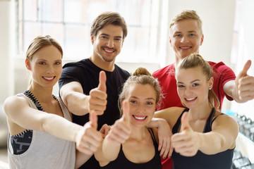 lächelnde sportler im studio zeigen daumen hoch