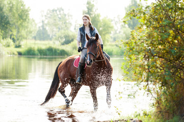 Young teenage girl riding horseback in river at early morning
