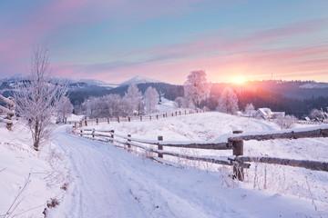 Zimowy wiejski krajobraz z drewna ogrodzenia i zaśnieżonej drodze