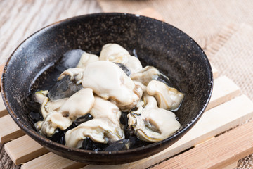 Opened Oysters on dark bowl on  wood background