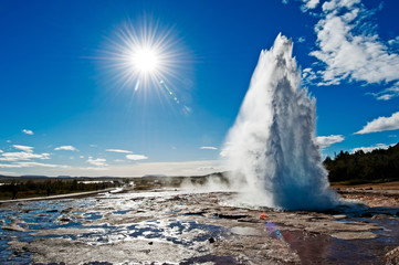 Back lit of Stokkur geyser with sunburst. Strokkur is a fountain geyser located in a geothermal area beside the Hvita River in Iceland in the southwest part of the country, east of Reykjavík.
