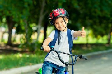 Little boy learns to ride a bike in thepark near the home. Kid shows the thumbs up on bicycle. Happy smiling child in helmet riding a cycling.