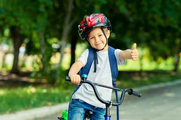 Mały chłopiec uczy się jeździć na rowerze w parku w pobliżu domu. Dziecko pokazuje kciuki do góry na rowerze. Szczęśliwy uśmiechnięty dziecko jedzie kolarstwo w hełmie.