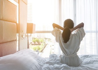 Life balance and relaxation concept with young Asian girl lifestyle simply waking up in the morning take it easy having some rest in luxury hotel room or home bedroom