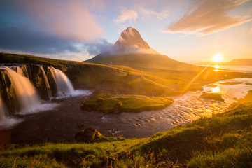 Summer sunrise on famous Kirkjufellsfoss Waterfall and Kirkjufell mountain in Iceland