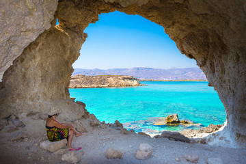 Amazing summer view of woman in a cave at Koufonisi island with magical turquoise waters, lagoons, tropical beaches of pure white sand and ancient ruins on Crete, Greece