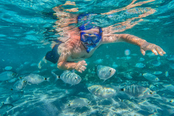 Young man snorkeling in underwater coral reef on tropical island