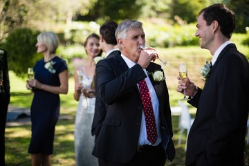 Guests having champagne while attending wedding