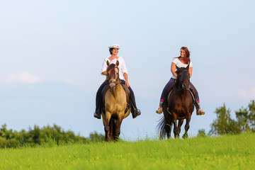 two women ride Andalusian horses