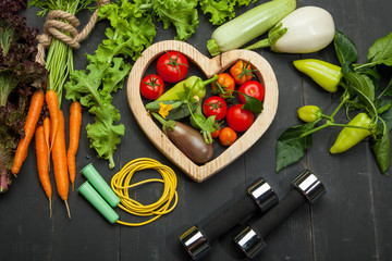 Fresh vegetables, diet and sport on a black wooden background