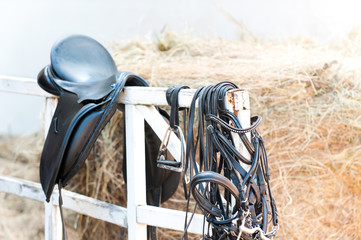 Black leather equestrian sport equipment and accessories hanging on fence