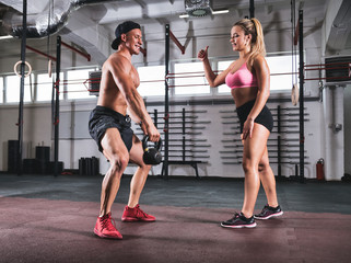 Muscular man doing kettlebell exersice with assistance of trainer in gym
