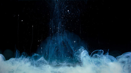 White paint drop mixing in water towards to camera. Ink swirling underwater. Cloud of ink isolated on black background. Abstract smoke explosion effect with particles.