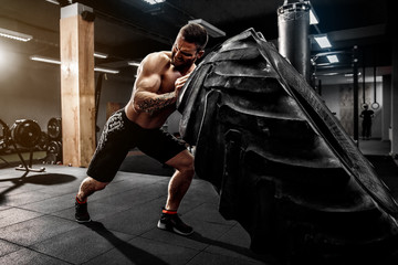 Shirtless man flipping heavy tire at crossfit gym