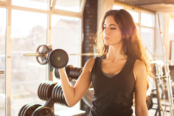 Portrait of athletic young woman training with a weight in the gym