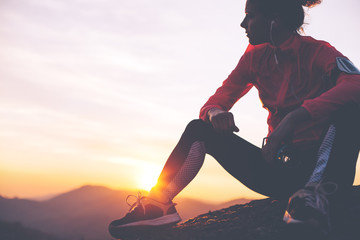 Silhouette of athletic girl resting after a hard training in the mountains at sunset. Sport tight clothes.