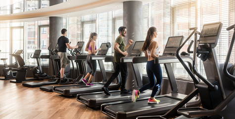 Group of four people, men and women, running on treadmills in modern and luminous fitness gym