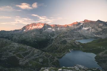 Wysokogórskie alpejskie jezioro, tamy i zbiorniki wodne w idyllicznej krainie z majestatycznymi skalistymi szczytami górskimi świecącymi o zachodzie słońca. Szeroki kąt widzenia na Alpy.