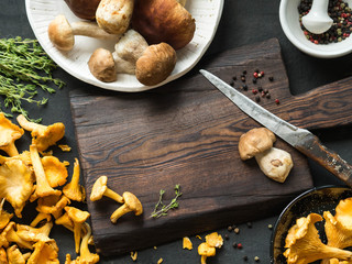 Raw wild chanterelle mushrooms and raw porcini mushrooms ready for cooking next to a dark board. Composition with wild mushrooms. Copy space
