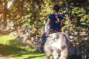 Horse rider woman riding near forest, horsewoman sport wear