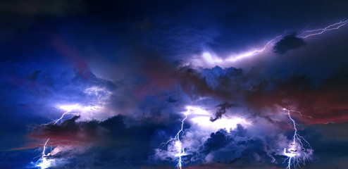 Thunderstorm clouds with lightning at night.