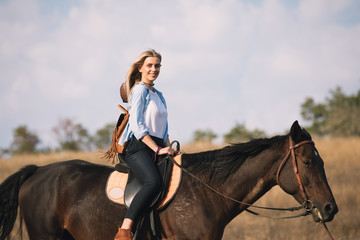 Beautiful young cowgirl riding her horse in field