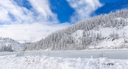 Beautiful lake Amut in taiga hills on Far East of Russia in early october. Mountain lake in winter. Beautiful nature. Snowy weather