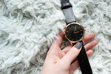 Elegant black watch in a female hand. Fashionable concept