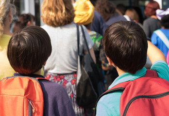 Two boys with backpacks look through a crowd in front of themselves and talk. School friendship.