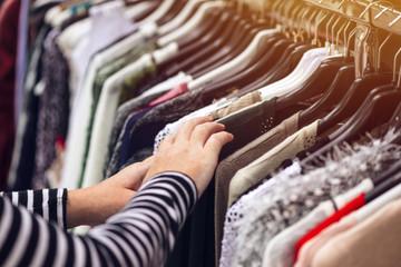 Kobieta przegląda odzież z drugiej ręki ulicy rynku